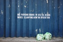 Two garbage bags by blue metal fence with signage