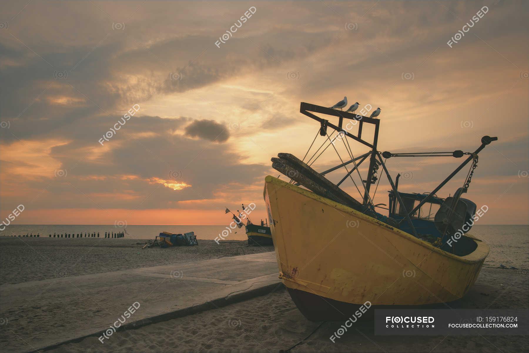 Heure du coucher du soleil sur la plage avec le bateau jaune photo 159176824 - Heures coucher du soleil ...