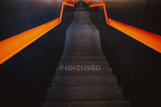 Black staircase with orange zigzag handrails on black walls — Stock Photo
