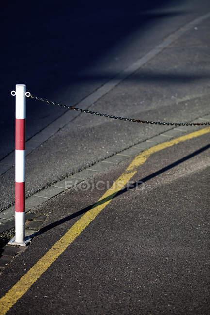 Passerelle d'asphalte avec bollard et chaîne — Photo de stock