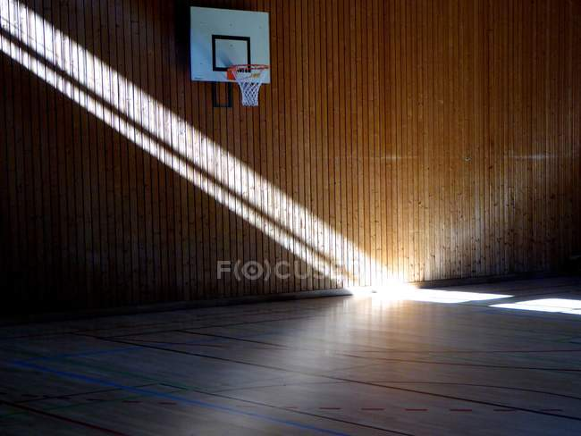 Sun beam in gymnasium by basketball basket — Stock Photo