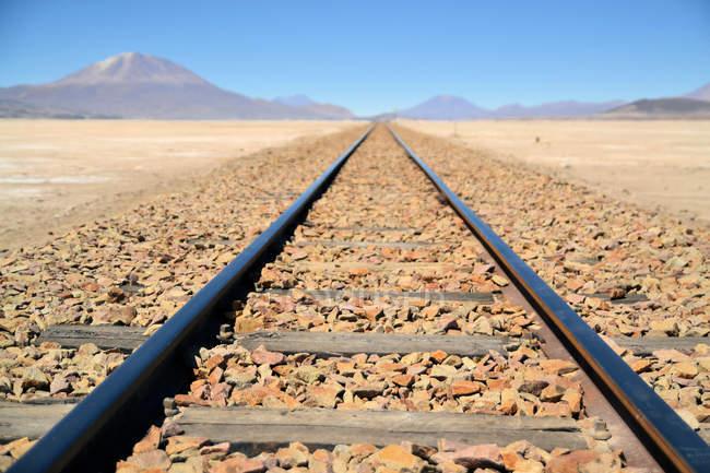Vías del tren sin fin en el desierto con una vista al volcán en el fondo, Bolivia - foto de stock
