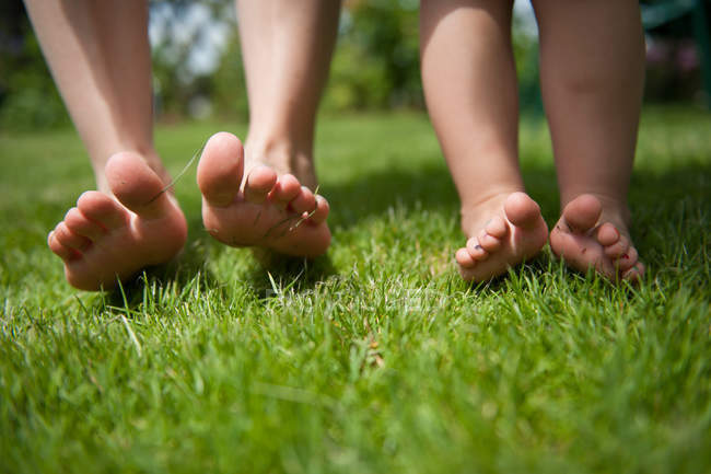 Young woman and baby feet by green grass lawn, closeup view — Stock Photo