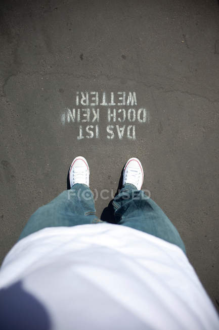 Partial view of man in jeans and sneakers looking dow at warning signage on ground — Stock Photo