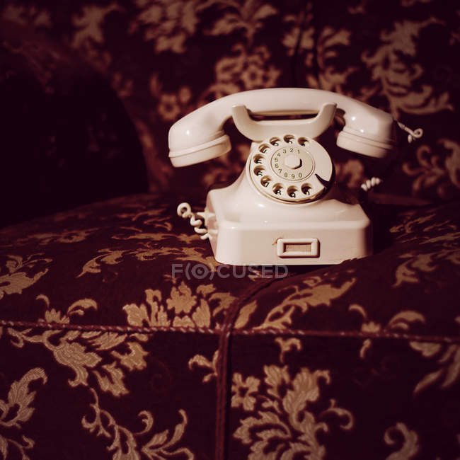 White old fashioned telephone with rotary dial on armchair — Stock Photo