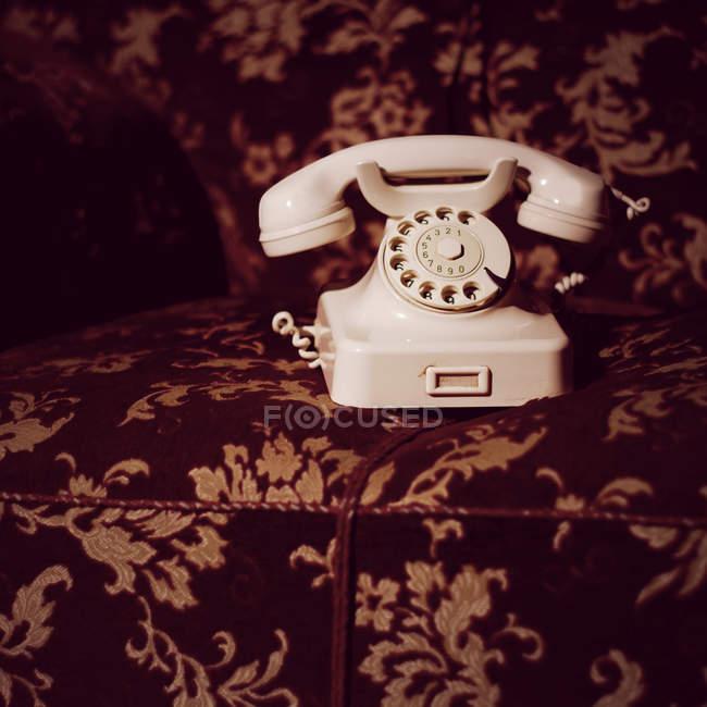 Weiße alte altmodisches Telefon mit Wählscheibe auf Sessel — Stockfoto