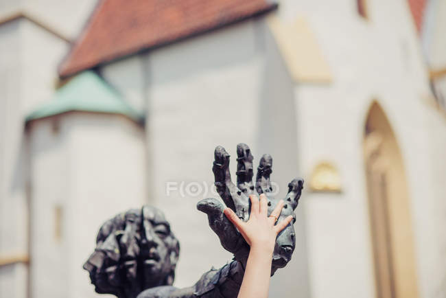 Child hand on hand of sculpture in Herford, Germany — Stock Photo