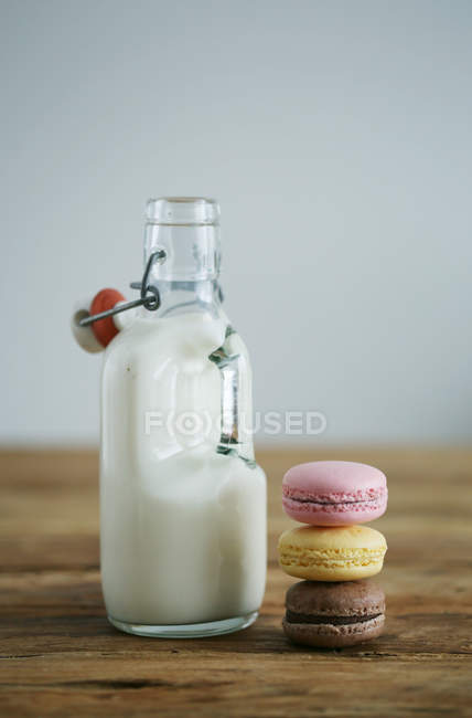Bottle with milk and cookies pile — Stock Photo
