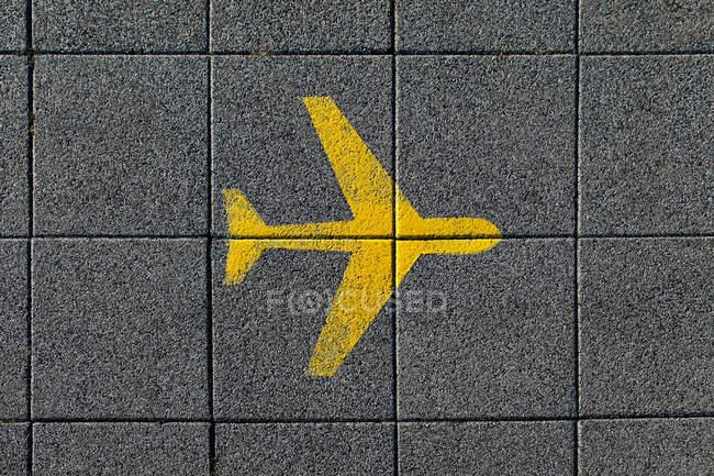 Yellow airplane on ground tiles — Stock Photo