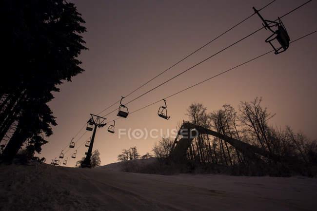 Cuesta de la montaña y ski lift al atardecer - foto de stock