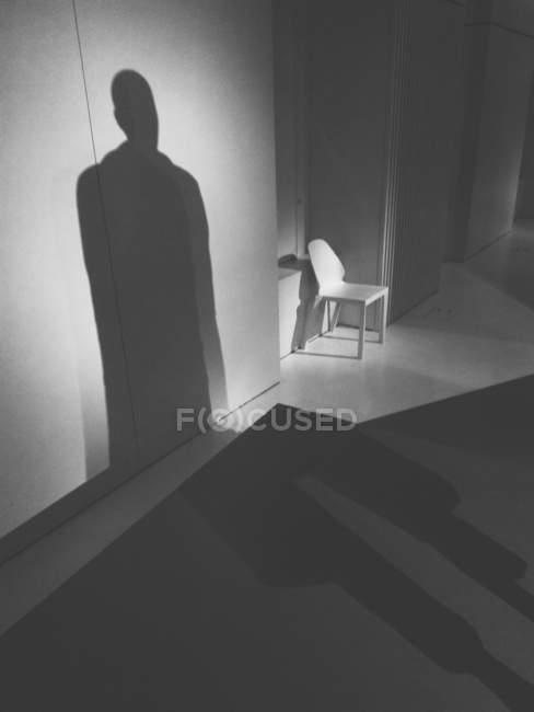 Tiro de interior escuro com sombra humana e cadeira — Fotografia de Stock