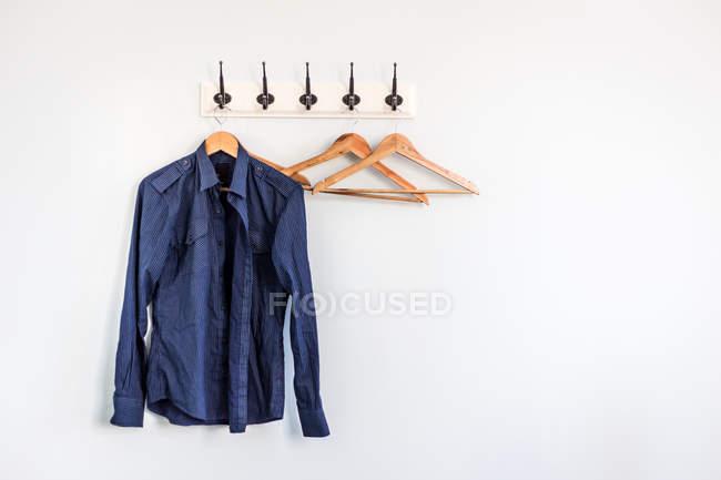Синій сорочці висить на білій стіні — стокове фото