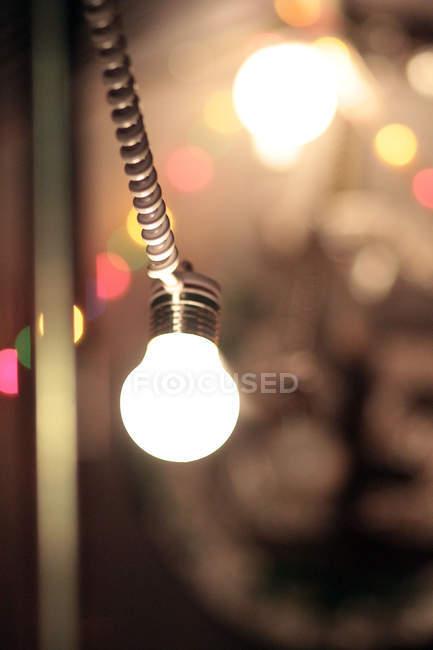 Closeup de bulbo brillante brillante, multicolor luces de fondo - foto de stock