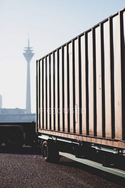 Recipiente no caminhão e torre de telecomunicações Rheinturm no fundo. Dusseldorf, Alemanha — Fotografia de Stock