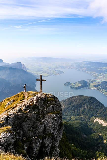 Personne avec vue sur la beauté de la nature en haut des montagnes avec croix — Photo de stock