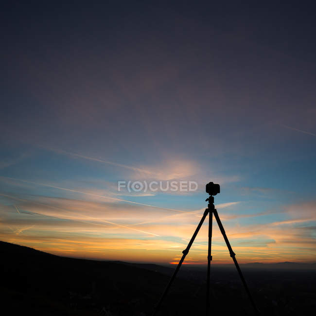 Photo camera on tripod silhouette and sunset sky view — Stock Photo