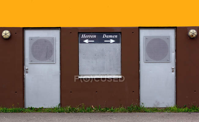 Daytime view of Herren and Damen signs with arrows pointing on doors of public toilet — Stock Photo