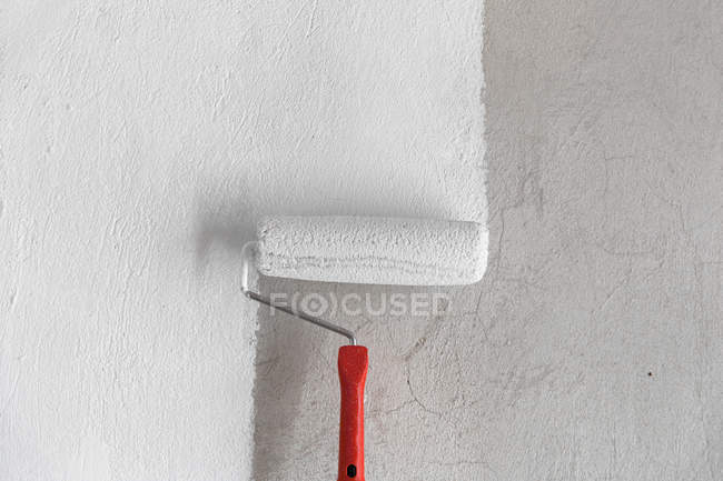 Painting wall in white with paint roller — Stock Photo