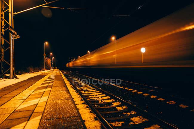 Bahnhof in der Nacht und Zug in Bewegungsunschärfe vorbei — Stockfoto