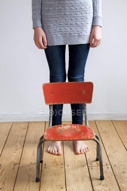 Cropped view of barefoot girl standing on wooden floor near shabby red chair — Stock Photo