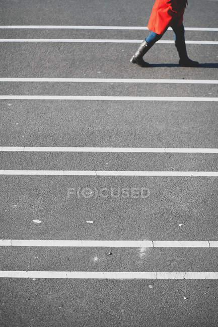 Recadrée vue de personne qui marche sur la route asphaltée bordée en journée — Photo de stock