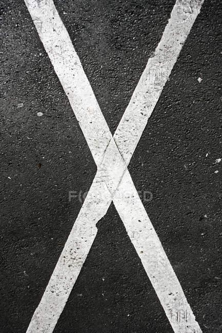 Vue de dessus de X blanc en forme de marquage sur la surface asphaltée — Photo de stock