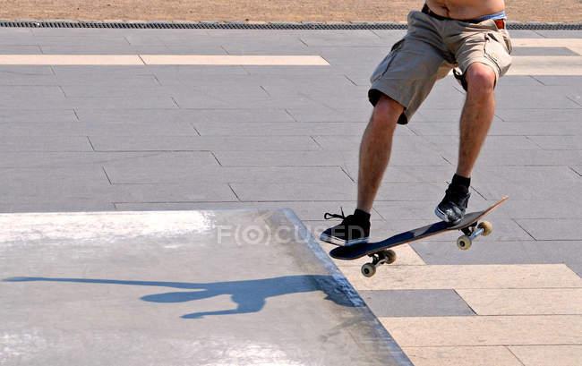 Recadrée de l'homme de faire le truc avec la planche à roulettes — Photo de stock