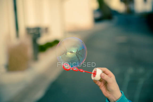 Child hand holding stick with colorful soap bubble — Stock Photo