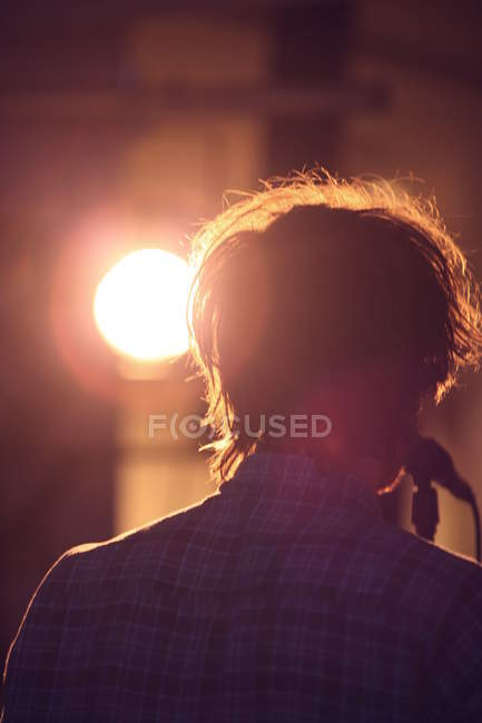 Rear view of male singer with microphone in the stage lights — Stock Photo