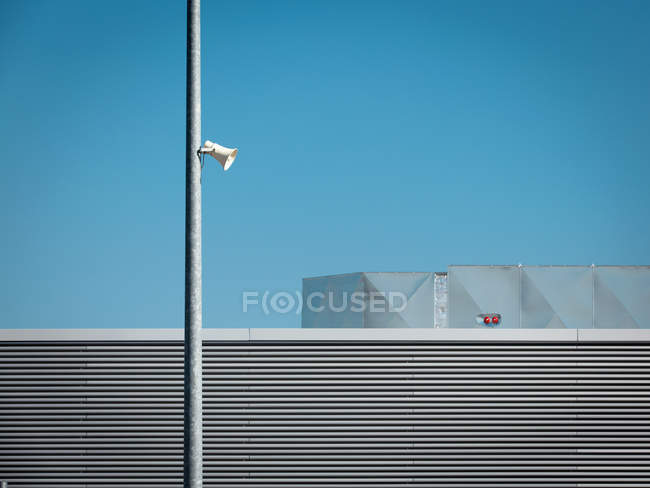 Daytime view of loudspeaker on broadcasting tower near building — Stock Photo