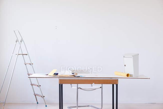 Quarto branco com diferentes objetos na mesa, a cadeira e a escada — Fotografia de Stock