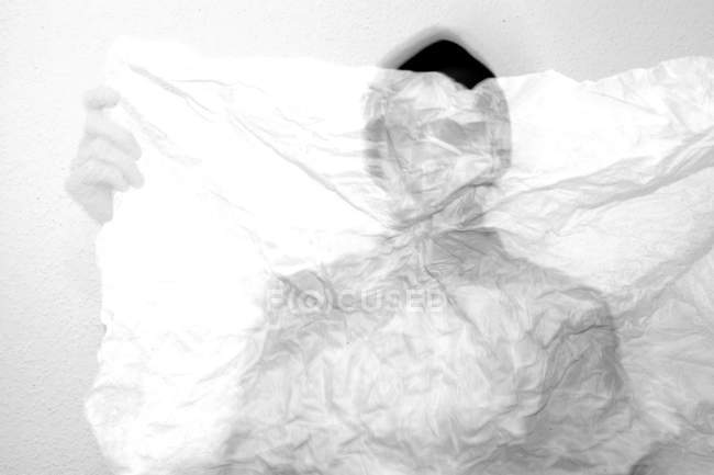 Front view of man hiding behind crumpled paper — Stock Photo