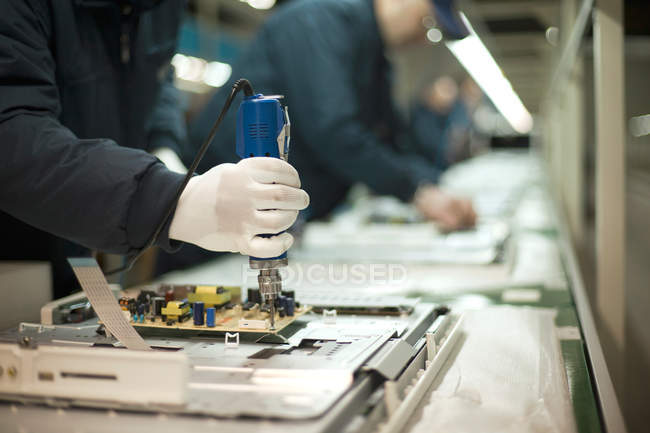 Cropped view of people working on production of television sets — Stock Photo