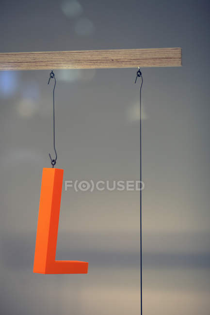 Advertising orange letter L hanging on thread — Stock Photo