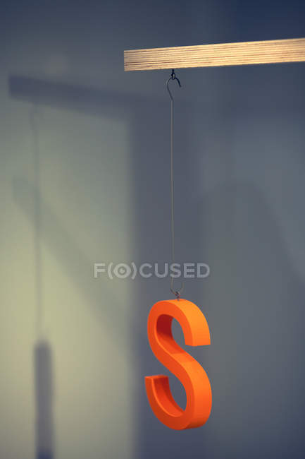 Advertising orange letter S hanging on thread — Stock Photo