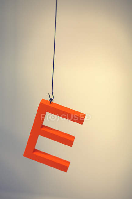 Closeup view of orange E letter hanging on wire — Stock Photo