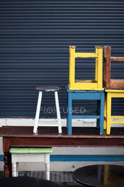 Daytime view of old colored chairs piled on wooden table — Stock Photo