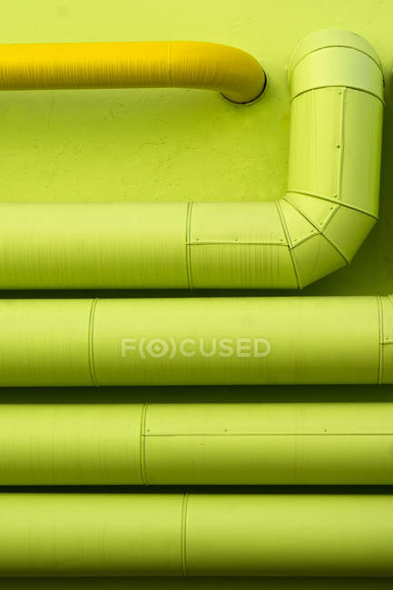 Top view of green and yellow pipes on wall — Stock Photo