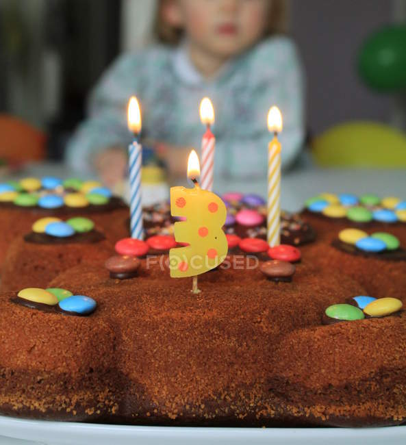 Birthday cake with burning candles, candle shaped number three, toddler girl on background — Stock Photo