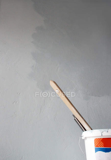 Daytime view of paint bucket with brushes near gray concrete wall — Stock Photo