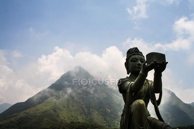 Buddhist statue in front of mountain peak — Stock Photo