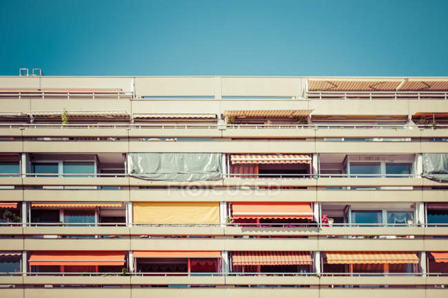 Colorful balconies of residential building and blue sky — Stock Photo