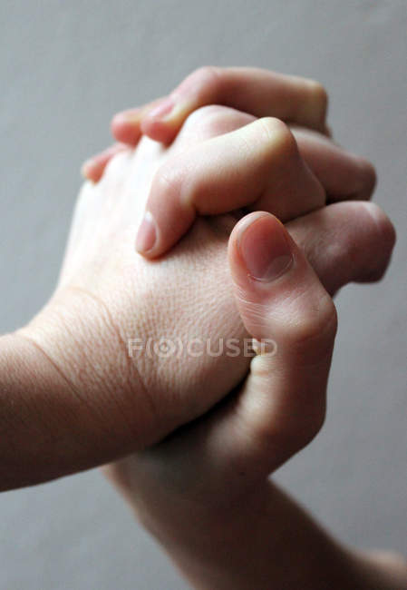 Close-up view of mother and child holding hands — Stock Photo