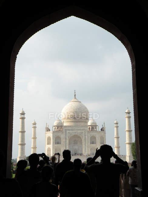 Vista posteriore di un gruppo di turisti scattare foto del Taj Mahal da costruzione arco — Foto stock