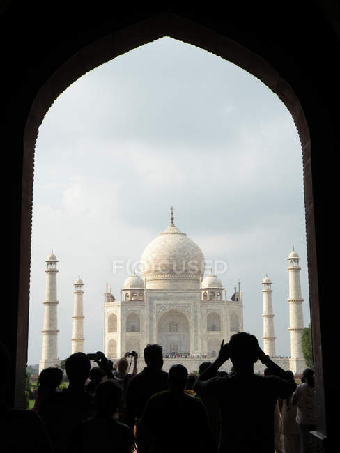Rear view of group of tourists taking photos of Taj Mahal from building arch — Stock Photo