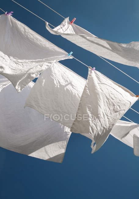 Clothesline with drying clothing bottom view in bright sunshine — Stock Photo