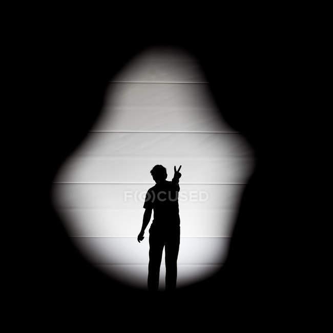 Une seule personne silhouette ombre montrer signe de paix avec les doigts — Photo de stock