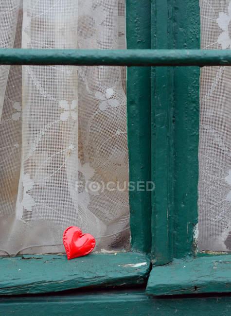 Coeur rouge en plastique sur la lucarne verte — Photo de stock