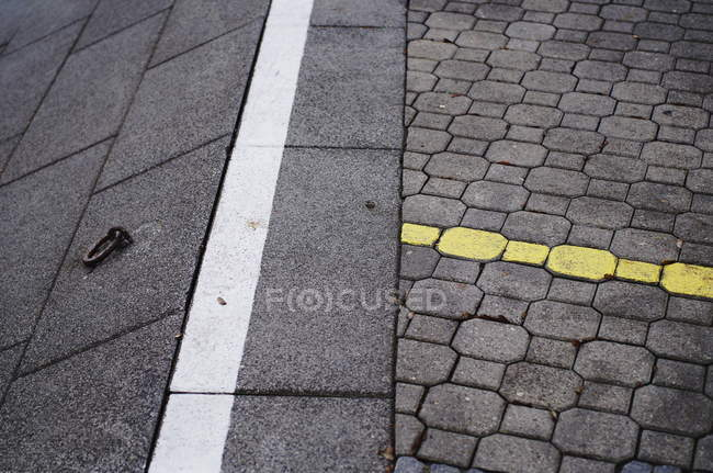 Daytime view of yellow marking on cobblestone road and white dividing line — Stock Photo