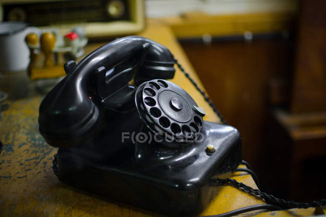 Black old fashioned telephone with rotary dial on table — Stock Photo